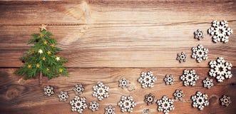 Julgran på träbräde med många snöflingor royaltyfria bilder