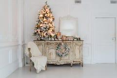 Julgran på träbyråbyråbyrå i den vita inre som dekoreras med konstgjorda blommor, girlander och leksaker Arkivfoton