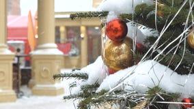 Julgran som dekoreras med bollar och leksaker Hon står på gatan, det snöar I bakgrunden det festligt lager videofilmer