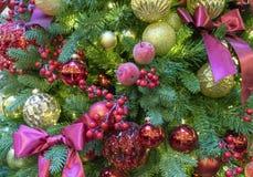 Julgran som dekoreras med färgrika leksakerpilbågar och bär vita röda stjärnor för abstrakt för bakgrundsjul mörk för garnering m arkivbilder