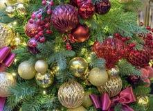 Julgran som dekoreras med färgrika leksakerpilbågar och bär vita röda stjärnor för abstrakt för bakgrundsjul mörk för garnering m arkivfoton