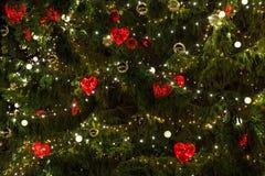 Julgran som dekoreras med heards och ljus Arkivbilder