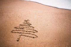 Julgran som dras i sand på stranden royaltyfri bild