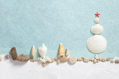 Julgran som göras från snäckskal på en blått- och vitbokbakgrund Royaltyfria Foton