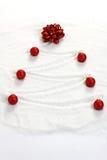 Julgran som målas i snö med den röda pilbågen och röda matt julbollar Arkivfoto