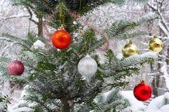Julgran utanför i snön som dekoreras med julleksaker Royaltyfri Bild