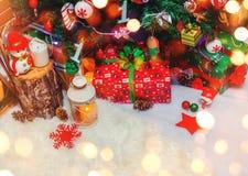 Julgranbakgrund och julpynt med snö, gåvor, suddigt som gristrar lyckligt nytt år för kort Vinterferie och Xm Arkivfoto