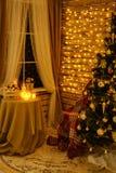 Julgranen är i rummet på de hängande girlanderna för väggen, en tabell vid fönstret med stearinljus arkivbild