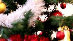 Julgranen dekorerade med röda struntsaker, den vita och röda girlanden, den guld- stjärnan och klirrklockor stock video