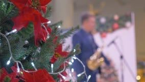 Julgranen dekoreras i en köpcentrum I bakgrunden spelar musikern saxofonen grönska för abstraktionbakgrundsgentile arkivfilmer