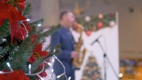 Julgranen dekoreras i en köpcentrum I bakgrunden spelar musikern saxofonen grönska för abstraktionbakgrundsgentile stock video