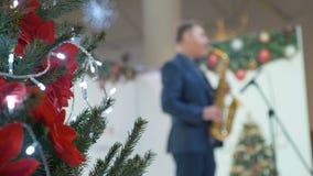 Julgranen dekoreras i en köpcentrum I bakgrunden spelar musikern saxofonen grönska för abstraktionbakgrundsgentile lager videofilmer