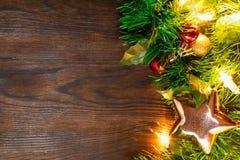 Julgranen med bollar, den guld- stjärnan och girlanden av gula ljus ligger på den mörka bruna trätabellen, bakgrund royaltyfria foton