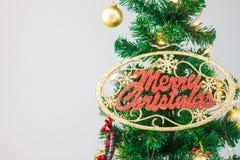 Julgranen med glödande tillbehör och GLAD JUL undertecknar Arkivfoto