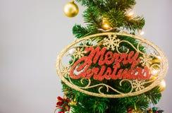 Julgranen med glödande tillbehör och GLAD JUL undertecknar Royaltyfri Bild