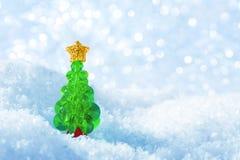 Julgranen på snö flagar ljusbakgrund, blått Xmas-träd arkivfoton