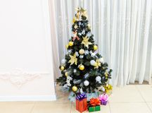 Julgranen som dekoreras med, leker med gåvor i askar under den på en ljus bakgrund royaltyfria bilder