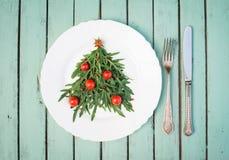 Julgranen som göras av arugula, och körsbärsröda tomater på vit plat Arkivbild