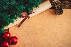 Julgranfilial, tre röda bollar, kottar och snirkelpapper med en pilbåge på bakgrunden för xmas för tabellkopieringsutrymme arkivfoton