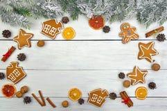 Julgranfilialer i snö och festliga kakor med kryddor royaltyfria foton