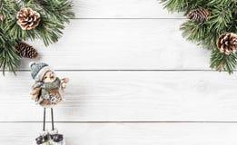 Julgranfilialer med sörjer kottar och julgarnering på vit träbakgrund Tema för Xmas och för lyckligt nytt år royaltyfri fotografi