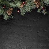 Julgranfilialer med sörjer kottar på mörk svart bakgrund Kort för Xmas och för lyckligt nytt år, bokeh, gristra som glöder royaltyfria bilder