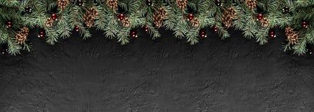 Julgranfilialer med sörjer kottar på mörk svart bakgrund Kort för Xmas och för lyckligt nytt år, bokeh, gristra som glöder arkivbilder
