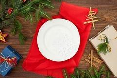 Julgranfilialer och platta på en röd servett royaltyfri foto