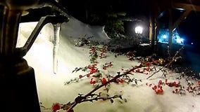 Julgranfilialer och röda bär på en lykta under en fallande snö arkivfilmer