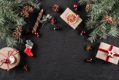 Julgranfilialer, sörjer kottar, gåvor på mörk bakgrund Tema för Xmas och för nytt år , snö Lekmanna- lägenhet, bästa sikt, royaltyfri bild