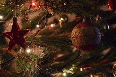 Julgrangarnering med röda bollstjärnor och också shinning guld Arkivfoto