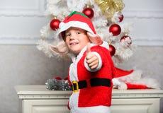 Julgranidéer för ungar Pojkeunge som nära kläs som vita konstgjorda öron för gullig varelse för älva magisk och den röda hatten royaltyfri fotografi