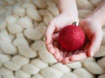 Julgranleksaker som röd boll i händer på bästa sikt för ull med kopieringsstället royaltyfria foton