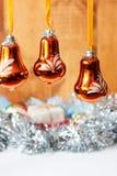 Julgranleksaker - stora blått sätter en klocka på med bergkristaller, skinande guld- små klockor på skinande glitter och träbakgr Arkivbild