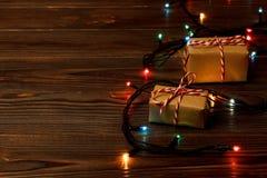 Julgranljus på golvet, lite varstans som en utmärkt slågen in grupp av gåvaaskar ställde in under en julgran Royaltyfri Fotografi