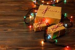 Julgranljus på golvet, lite varstans som en utmärkt slågen in grupp av gåvaaskar ställde in under en julgran Royaltyfri Foto