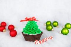 Julgranmuffin med den vita fondantglasyren på kaka Arkivbilder