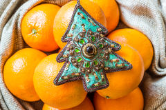 Julgranprydnad och apelsiner i säck Royaltyfri Bild