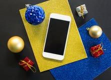 Julgranprydnad och plan sammansättning för smartphone på den svarta trätabellen Arkivbild