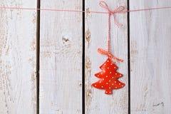 Julgranprydnad som hänger över vit träbakgrund Arkivbilder
