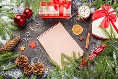 Julgranträd i snö med kottar, anisstjärnor, kanelbruna pinnar, tappningklockan, dekorativa stjärnor, julbollar och giftbo Royaltyfria Foton