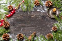 Julgranträd i snö med kottar, det röda bandet och stearinljuset i ljusstake på ett mörkt träbräde kopiera avstånd för din text Arkivbilder
