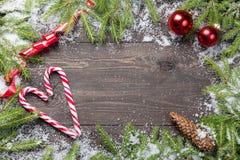 Julgranträd i snö med kotten, det röda bandet, röda bollar för jul och godisrottingar på ett mörkt träbräde Kopieringsutrymme för Arkivbild