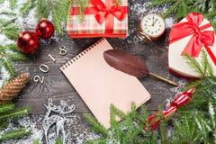 Julgranträd i snö med kotten, tappningklockan, jul klumpa ihop sig, giftboxes på ett mörkt träbräde Tom anteckningsbok med qull Fotografering för Bildbyråer