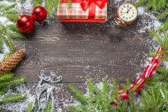 Julgranträd i snö med kotten, tappningklockan, julbollar, giftbox och hjortar på ett mörkt träbräde Kopieringsutrymme för dig Royaltyfri Foto