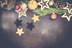 Julgranträd med garnering på det mörka träbrädet, pepparkakakakastjärnor kopiera avstånd arkivbilder
