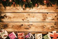 Julgranträd med garneringar och gåvaaskar på mörkt träbräde Fotografering för Bildbyråer