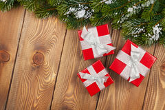 Julgranträd med snö och röda gåvaaskar på lantligt trä Arkivbilder