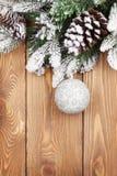 Julgranträd med snö och struntsak på lantligt träbräde Royaltyfria Bilder