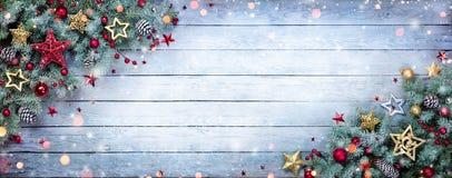 Julgranträd med struntsaker och snöflingor på trä royaltyfria foton